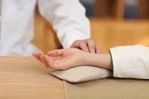 Joël SPISSER praticien de MTC qui prend le pouls à un patient